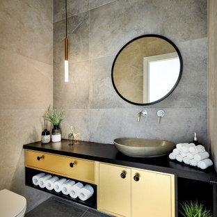 テルアビブの中サイズのコンテンポラリースタイルのおしゃれなバスルーム (浴槽なし) (フラットパネル扉のキャビネット、黄色いキャビネット、壁掛け式トイレ、グレーのタイル、磁器タイル、磁器タイルの床、ベッセル式洗面器、グレーの床、黒い洗面カウンター) の写真