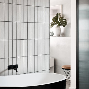 Photo of a contemporary bathroom in Melbourne with a freestanding tub, white tile, cement tile, white walls, terrazzo floors and grey floor.