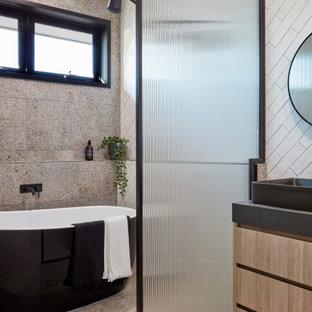 Идея дизайна: главная ванная комната в современном стиле с плоскими фасадами, фасадами цвета дерева среднего тона, отдельно стоящей ванной, душевой комнатой, белой плиткой, плиткой кабанчик, полом из терраццо, настольной раковиной, коричневым полом и черной столешницей