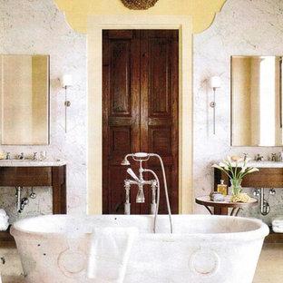 Modelo de cuarto de baño principal, mediterráneo, de tamaño medio, con armarios abiertos, puertas de armario de madera en tonos medios, bañera exenta, baldosas y/o azulejos grises, baldosas y/o azulejos blancos, baldosas y/o azulejos de piedra, paredes amarillas, suelo de cemento y encimera de esteatita
