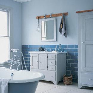サンフランシスコの中サイズのトラディショナルスタイルのおしゃれなバスルーム (浴槽なし) (落し込みパネル扉のキャビネット、青いキャビネット、置き型浴槽、分離型トイレ、ガラスタイル、青い壁、磁器タイルの床、アンダーカウンター洗面器、珪岩の洗面台) の写真