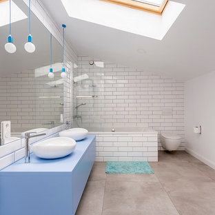 This is an example of a contemporary bathroom in London with flat-panel cabinets, blue cabinets, a built-in bath, a shower/bath combination, a wall mounted toilet, white tiles, white walls, a vessel sink, grey floors and blue worktops.
