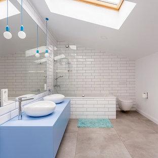 Идея дизайна: ванная комната в современном стиле с плоскими фасадами, синими фасадами, накладной ванной, душем над ванной, инсталляцией, белой плиткой, белыми стенами, настольной раковиной, серым полом и синей столешницей