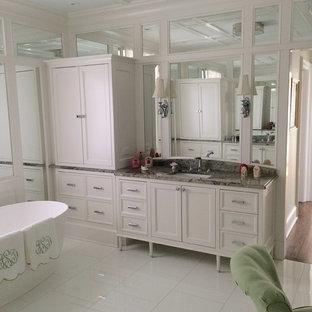 Ejemplo de cuarto de baño principal, minimalista, grande, con armarios con paneles empotrados, puertas de armario blancas, bañera exenta, baldosas y/o azulejos con efecto espejo, paredes blancas, suelo de mármol, lavabo bajoencimera, encimera de granito y suelo blanco