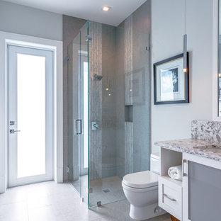 Idéer för att renovera ett mellanstort vintage badrum med dusch, med vita skåp, en hörndusch, en toalettstol med hel cisternkåpa, grå kakel, porslinskakel, grå väggar, klinkergolv i porslin, ett undermonterad handfat, bänkskiva i kvartsit, luckor med glaspanel, vitt golv och dusch med gångjärnsdörr