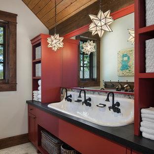 Imagen de cuarto de baño infantil, rural, con armarios abiertos, puertas de armario rojas, paredes blancas, lavabo de seno grande, suelo gris, encimeras negras, suelo de baldosas tipo guijarro y encimera de granito