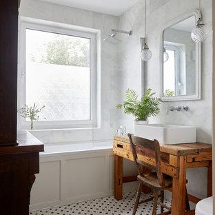 ロンドンのエクレクティックスタイルのおしゃれなバスルーム (浴槽なし) (家具調キャビネット、中間色木目調キャビネット、アルコーブ型浴槽、シャワー付き浴槽、白いタイル、モザイクタイル、ベッセル式洗面器、木製洗面台、マルチカラーの床、オープンシャワー、ブラウンの洗面カウンター) の写真