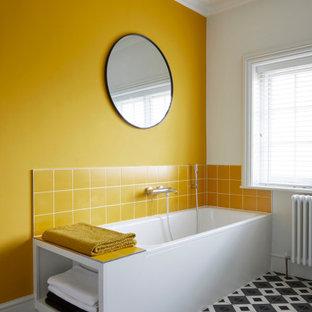 Cette image montre une salle de bain design avec une baignoire d'angle, un carrelage jaune, un mur jaune et un sol multicolore.