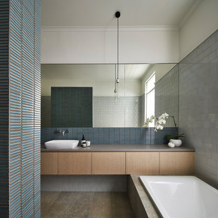 This is an example of a contemporary bathroom in Sydney with medium wood cabinets, a drop-in tub, blue tile, gray tile, white walls, a vessel sink and grey floor.