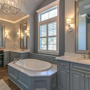 Foto de cuarto de baño principal, de estilo americano, grande, con armarios con paneles con relieve, puertas de armario grises, bañera encastrada, paredes grises, suelo de madera oscura, lavabo bajoencimera, encimera de mármol y suelo marrón