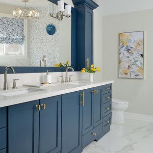 Diseño de cuarto de baño principal, tradicional renovado, grande, con puertas de armario azules, bañera exenta, baldosas y/o azulejos blancos, baldosas y/o azulejos de mármol, paredes grises, suelo de baldosas de cerámica, encimera de cuarzo compacto, suelo blanco, encimeras blancas, armarios con paneles empotrados y lavabo bajoencimera