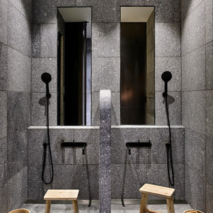 Modern bathroom with a curbless shower, gray tile, grey walls, grey floor and an open shower.