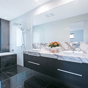 Design ideas for a large contemporary master bathroom in Brisbane with flat-panel cabinets, black cabinets, an open shower, black and white tile, white walls, a vessel sink, black floor, an open shower, ceramic floors, engineered quartz benchtops, grey benchtops, a two-piece toilet and ceramic tile.