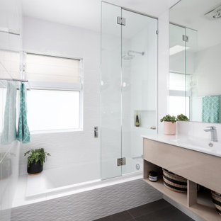 Inspiration for a contemporary bathroom in Brisbane with flat-panel cabinets, light wood cabinets, a drop-in tub, white tile, an integrated sink, grey floor, white benchtops, a single vanity and a floating vanity.