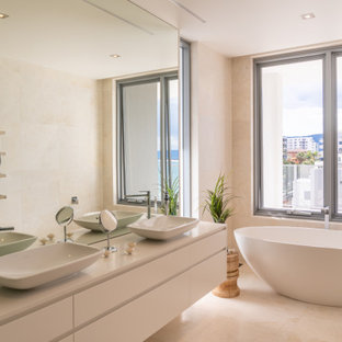 Inspiration for a contemporary bathroom in Other with flat-panel cabinets, white cabinets, a freestanding tub, a vessel sink, beige floor and white benchtops.