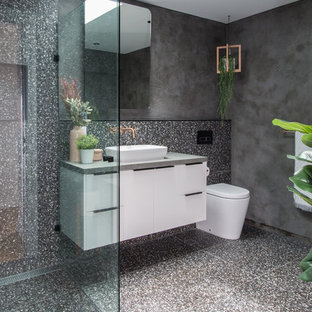 Photo of a contemporary 3/4 bathroom in Brisbane with flat-panel cabinets, white cabinets, a corner shower, a one-piece toilet, gray tile, grey walls, a vessel sink, grey floor and grey benchtops.