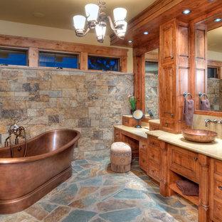 Rustik inredning av ett badrum, med ett fristående handfat, luckor med upphöjd panel, skåp i mellenmörkt trä och ett fristående badkar