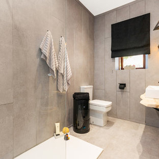 Photo of a medium sized contemporary bathroom in Other with a walk-in shower, a two-piece toilet, grey tiles, grey walls, a vessel sink, wooden worktops, grey floors, an open shower and beige worktops.