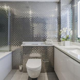 Пример оригинального дизайна интерьера: главная ванная комната в современном стиле с плоскими фасадами, белыми фасадами, полновстраиваемой ванной, инсталляцией, металлической плиткой, врезной раковиной и серым полом