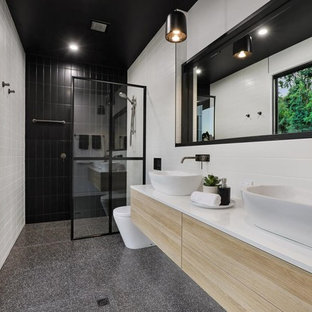 Design ideas for a contemporary bathroom in Sunshine Coast with flat-panel cabinets, light wood cabinets, a curbless shower, white tile, white walls, a vessel sink, grey floor, an open shower and white benchtops.
