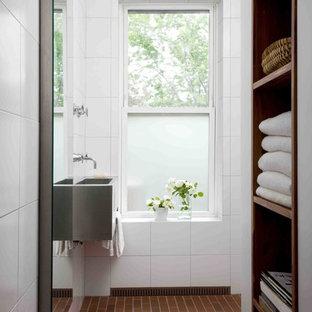 Inredning av ett modernt litet badrum, med ett väggmonterat handfat, vita väggar, öppna hyllor, bänkskiva i rostfritt stål, vit kakel, porslinskakel, tegelgolv, en kantlös dusch och skåp i mörkt trä