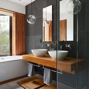 ニューヨークのコンテンポラリースタイルのおしゃれな浴室 (ベッセル式洗面器、木製洗面台、ドロップイン型浴槽、黒いタイル、スレートタイル、ブラウンの洗面カウンター) の写真