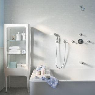 Immagine di una stanza da bagno minimalista con vasca freestanding, ante di vetro, ante bianche, vasca/doccia, piastrelle bianche e pavimento grigio