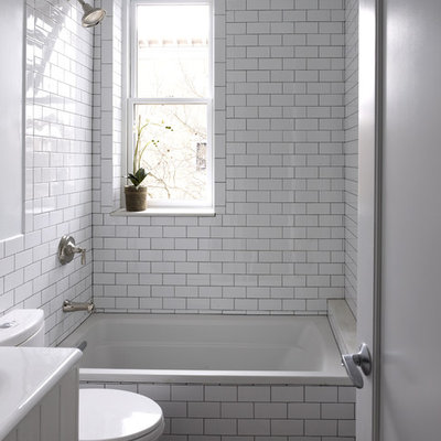 Example of a mid-sized trendy 3/4 white tile and subway tile marble floor bathroom design in New York with white cabinets, a two-piece toilet, furniture-like cabinets, white walls and a console sink