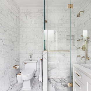 Corner shower - contemporary gray tile, white tile and marble tile marble floor corner shower idea in New York with shaker cabinets, white cabinets, a two-piece toilet, marble countertops, a hinged shower door and white countertops