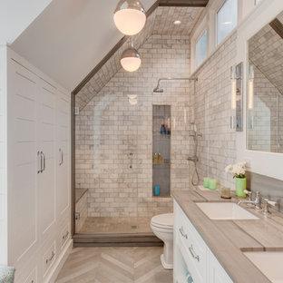 Landhaus Duschbad mit profilierten Schrankfronten, weißen Schränken, Duschnische, weißen Fliesen, weißer Wandfarbe, Unterbauwaschbecken, grauem Boden, Falttür-Duschabtrennung und grauer Waschtischplatte in Boston
