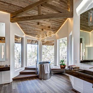 Foto de cuarto de baño principal, actual, con bañera japonesa, baldosas y/o azulejos blancos, paredes blancas, suelo de madera oscura, lavabo encastrado, encimera de madera, suelo marrón y encimeras marrones