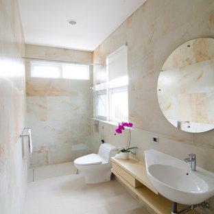 Diseño de cuarto de baño con ducha, de estilo zen, de tamaño medio, con armarios abiertos, puertas de armario de madera clara, ducha abierta, sanitario de una pieza, baldosas y/o azulejos beige, baldosas y/o azulejos de piedra, paredes beige, lavabo suspendido y encimera de laminado