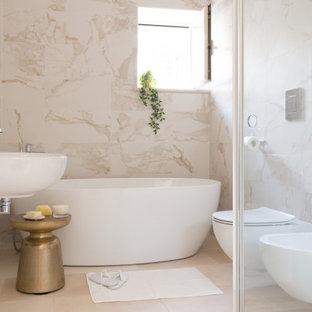 Esempio di una stanza da bagno design con vasca freestanding, piastrelle bianche, lavabo sospeso e pavimento beige