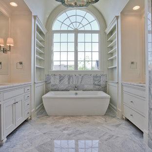 Foto på ett stort vintage en-suite badrum, med luckor med profilerade fronter, vita skåp, ett fristående badkar, vit kakel, en dusch i en alkov, marmorkakel, beige väggar, marmorgolv, ett undermonterad handfat, marmorbänkskiva, grått golv och dusch med gångjärnsdörr