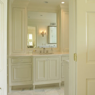 Elegant white tile bathroom photo in Birmingham with an undermount sink, recessed-panel cabinets and beige cabinets