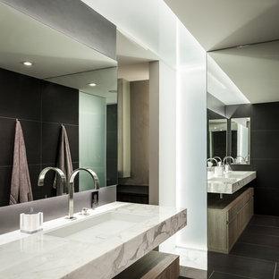 Idee per una grande stanza da bagno padronale minimalista con lavabo sottopiano, ante lisce, top in marmo, piastrelle nere, piastrelle in gres porcellanato, pavimento in gres porcellanato, ante grigie, vasca sottopiano, doccia a filo pavimento, WC sospeso, pareti nere e pavimento nero