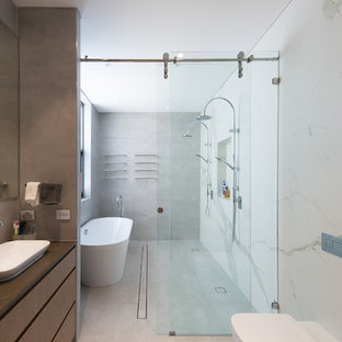 Large contemporary wet room bathroom in Sydney with flat-panel cabinets, medium wood cabinets, a freestanding tub, white tile, stone slab, a vessel sink, grey floor and grey benchtops.