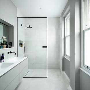 This is an example of a contemporary shower room in London with flat-panel cabinets, grey cabinets, a built-in shower, grey tiles, grey walls, an integrated sink, grey floors, an open shower and white worktops.