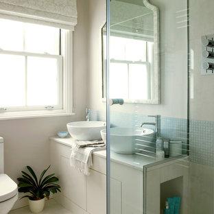 Modernes Badezimmer mit Aufsatzwaschbecken, Mosaikfliesen, beigem Boden und weißer Waschtischplatte in London