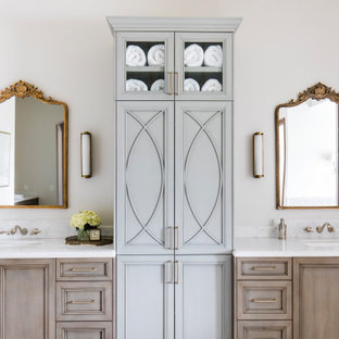 Example of a large tuscan master limestone floor, double-sink and coffered ceiling freestanding bathtub design in Phoenix with recessed-panel cabinets, marble countertops, a hinged shower door, a built-in vanity, beige cabinets, white walls, an undermount sink and white countertops
