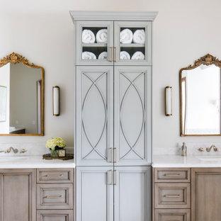На фото: большие главные ванные комнаты в средиземноморском стиле с фасадами с утопленной филенкой, отдельно стоящей ванной, полом из известняка, мраморной столешницей, душем с распашными дверями, тумбой под две раковины, встроенной тумбой, кессонным потолком, бежевыми фасадами, белыми стенами, врезной раковиной и белой столешницей