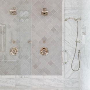 Cette image montre une douche en alcôve méditerranéenne avec un placard avec porte à panneau encastré, des portes de placard bleues, une baignoire indépendante, un sol en calcaire, un plan de toilette en marbre, une cabine de douche à porte battante, meuble double vasque, meuble-lavabo encastré et un plafond à caissons.
