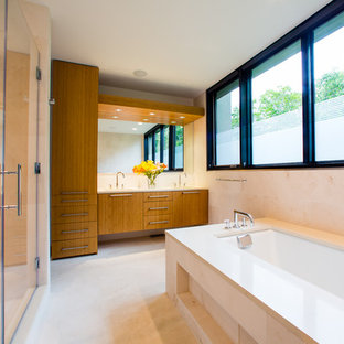 Design ideas for a medium sized contemporary ensuite bathroom in DC Metro with flat-panel cabinets, medium wood cabinets, a submerged bath, an alcove shower, beige tiles, ceramic tiles, beige walls, ceramic flooring, a submerged sink, solid surface worktops, beige floors and a hinged door.