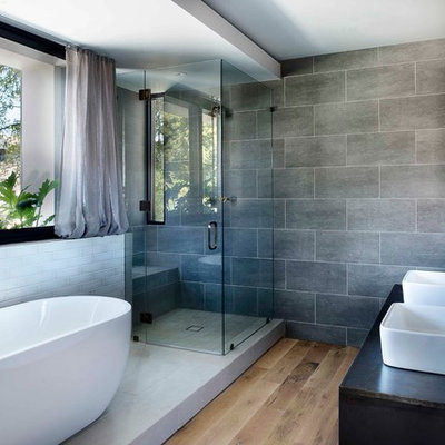 Inspiration for an industrial master gray tile light wood floor bathroom remodel in Atlanta with a vessel sink and a hinged shower door