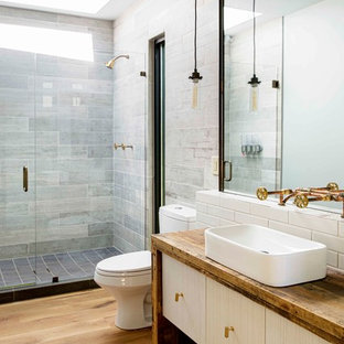 This is an example of an industrial 3/4 bathroom in Atlanta with flat-panel cabinets, light wood cabinets, gray tile, white tile, a vessel sink, wood benchtops, light hardwood floors and a hinged shower door.