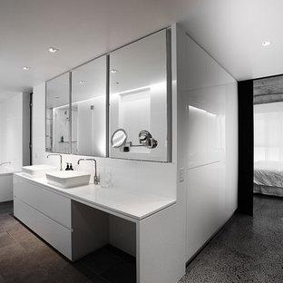 Idée de décoration pour une salle de bain design avec une vasque, un placard à porte plane, des portes de placard blanches et un mur blanc.