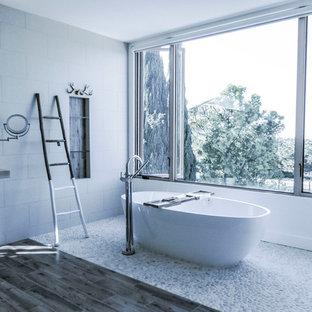 Modelo de cuarto de baño principal, moderno, extra grande, con bañera exenta, paredes blancas, armarios abiertos, baldosas y/o azulejos grises, suelo de baldosas tipo guijarro, suelo de baldosas de porcelana y lavabo sobreencimera