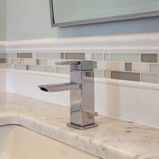 Aménagement d'une salle de bain principale bord de mer de taille moyenne avec un WC à poser, un carrelage blanc, des plaques de verre, un sol en carrelage de céramique, un lavabo encastré et un plan de toilette en marbre.