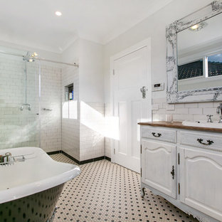 Inspiration for a traditional master bathroom in Melbourne with an integrated sink, furniture-like cabinets, distressed cabinets, wood benchtops, a claw-foot tub, a two-piece toilet, multi-coloured tile, porcelain tile, white walls, mosaic tile floors and an alcove shower.
