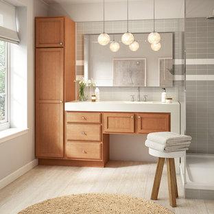 デンバーの中サイズのトランジショナルスタイルのおしゃれなマスターバスルーム (落し込みパネル扉のキャビネット、中間色木目調キャビネット、コーナー設置型シャワー、グレーのタイル、サブウェイタイル、白い壁、ラミネートの床、一体型シンク、珪岩の洗面台、ベージュの床、オープンシャワー) の写真